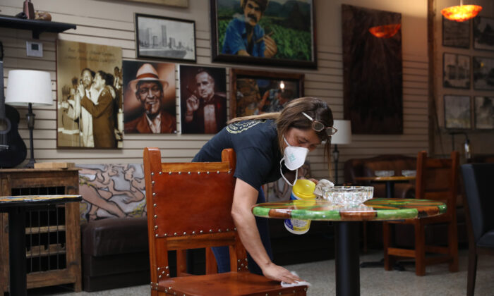 Una mujer limpia una mesa y las sillas en una tienda en Miami, Florida, el 19 de mayo de 2020. (Joe Raedle / Getty Images)