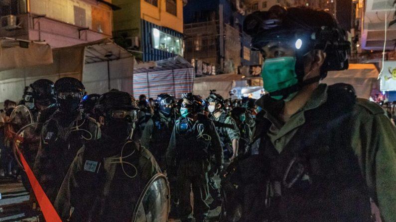Policía antidisturbios con mascarillas protectoras asegura un área durante una operación de control de multitudes en el distrito de Mongkok en Hong Kong, el 10 de mayo de 2020. (Anthony Kwan/Getty Images)