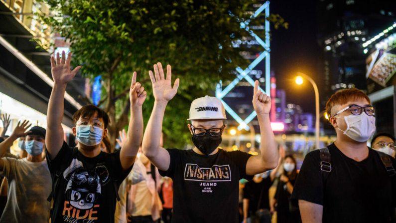 """Manifestantes prodemocracia hacen gestos con el eslogan """"cinco demandas y ni una menos"""" durante una vigilia fuera del centro comercial Pacific Place en la zona del Almirantazgo de Hong Kong el 15 de mayo de 2020, para conmemorar el aniversario de 11 meses desde que un hombre cayó desde un andamio, durante una protesta contra el proyecto de ley de extradición del gobierno de Hong Kong el año pasado. (Anthony Wallance/AFP vía Getty Images)"""