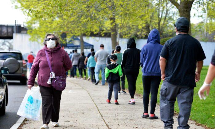 Las personas hacen fila para obtener sus kits de cuidado que contienen muchos artículos ahora difíciles de encontrar, incluyendo mascarillas, suministros de desinfección, artículos de cuidado personal y materiales educativos en la Escuela Secundaria Técnica de Lynn en Lynn, Massachusetts, el 16 de mayo de 2020. (Joseph Prezioso/AFP vía Getty Images)