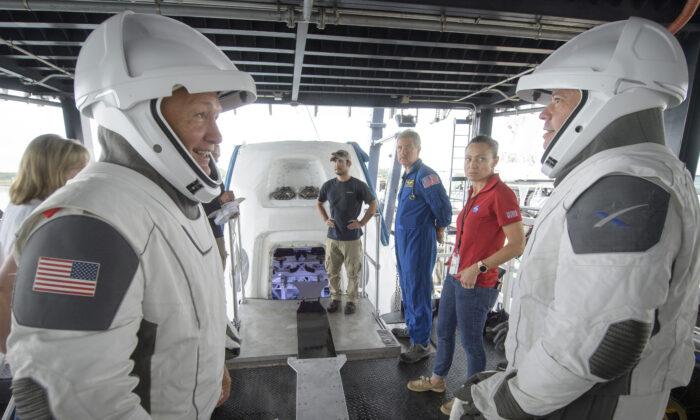 Los astronautas de la NASA Doug Hurley (I) y Bob Behnken trabajan con equipos de la NASA y SpaceX para ensayar la extracción de la tripulación del Crew Dragon de SpaceX, que se utilizará para llevar humanos a la Estación Espacial Internacional, en la Cuenca del Tridente en Cabo Cañaveral, Florida, el 13 de agosto de 2019. (Bill Ingalls/NASA)