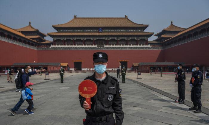 Un guardia chino lleva una mascarilla protectora mientras está de pie en la entrada de la Ciudad Prohibida, en Beijing, China, el 1 de mayo de 2020, abierta a visitantes limitados. (Kevin Frayer/Getty Images)