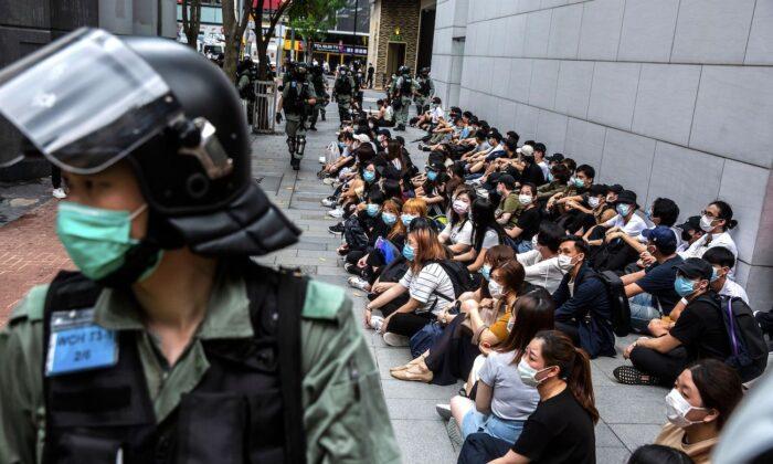 La policía antidisturbios detiene a un grupo de personas durante una protesta en el distrito de Causeway Bay de Hong Kong mientras la legislatura de la ciudad debate sobre una ley que prohíbe insultar al himno nacional de China el 27 de mayo de 2020. (Isaac Lawrence/AFP vía Getty Images)