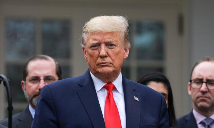 El presidente Donald Trump, flanqueado por funcionarios y líderes empresariales, anuncia una emergencia nacional con respecto al coronavirus en la Rosaleda de la Casa Blanca en Washington el 13 de marzo de 2020. (Charlotte Cuthbertson/The Epoch Times)