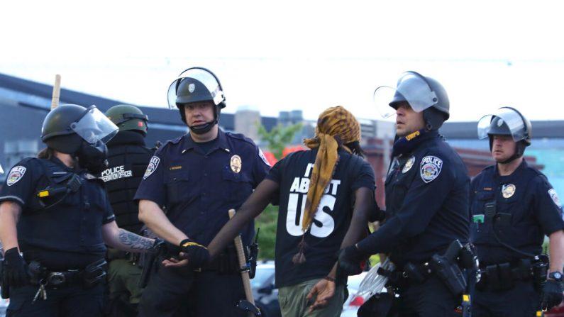 La policía estatal detiene a un manifestante después de permanecer fuera del toque de queda a las 8 pm del gobernador durante la sexta noche de protestas y violencia tras la muerte de George Floyd, en Minneapolis, Minnesota, el 31 de mayo de 2020. (Charlotte Cuthbertson/The Epoch Times)