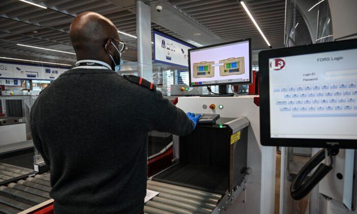 Un funcionario del aeropuerto revisa el equipaje de los pasajeros que pasan por una máquina de rayos X en la Terminal 3 del aeropuerto de Orly, en Orly, en las afueras de París, el 22 de junio de 2020. (BERTRAND GUAY/AFP a través de Getty Images)