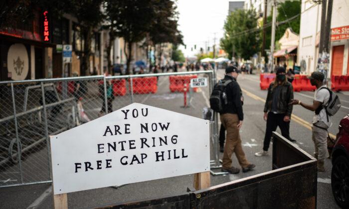 """Un cartel figura en una barrera a la entrada de la llamada """"Zona Autónoma de Capitol Hill"""" en Seattle, Wash., el 10 de junio de 2020. (David Ryder/Getty Images)"""