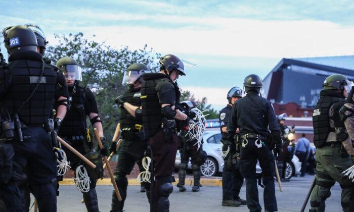 La policía estatal y local se prepara para arrestar a unos 100 manifestantes por su incumplimiento al toque del queda del gobernador durante la sexta noche de protestas y violencia tras la muerte de George Floyd, en Minneapolis, Minnesota, el 31 de mayo de 2020. (Charlotte Cuthbertson/The Epoch Times)
