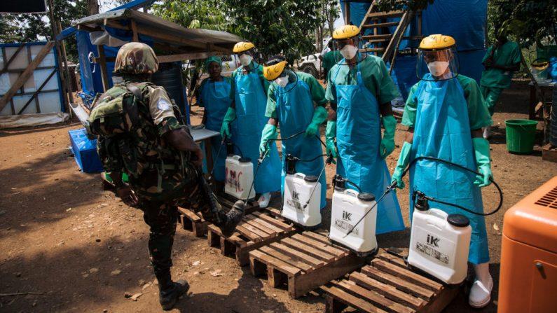 Un miembro de las fuerzas de mantenimiento de la paz de las Naciones Unidas se limpia los zapatos con una solución de cloro antes de salir de un centro de tratamiento del Ébola en Mangina, en la provincia de Kivu del Norte (La RD Congo), el 1 de septiembre de 2019. (Alexis Huguet/AFP vía Getty Images)