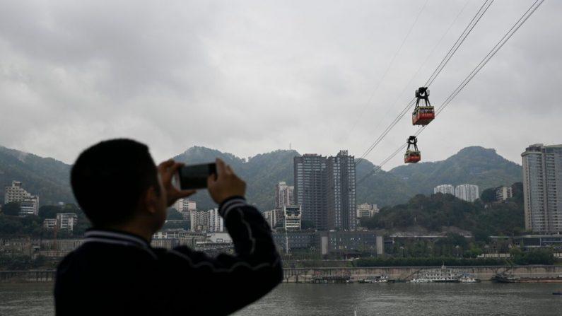 Un hombre tomando fotos en la ciudad de Chongqing, suroeste de China, el 22 de marzo de 2019. (WANG ZHAO/AFP a través de Getty Images)