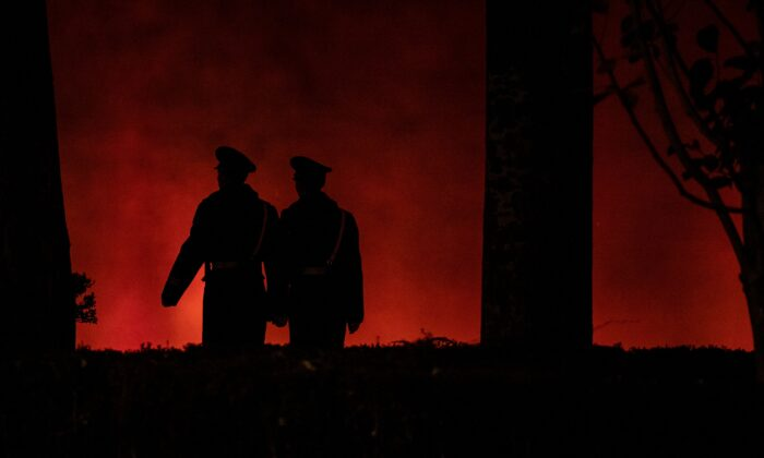 Policías paramilitares caminan por una pared roja cerca de la puerta de Tiananmen en Beijing, el 13 de noviembre de 2019. (NOEL CELIS/AFP a través de Getty Images)