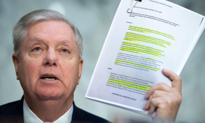 El presidente del Comité Judicial del Senado, Lindsey Graham (R-S.C.), sostiene una copia del Dossier Steele durante una audiencia del Comité Judicial del Senado, en el Capitolio, el 11 de diciembre de 2019. (Saul Loeb/AFP vía Getty Images)