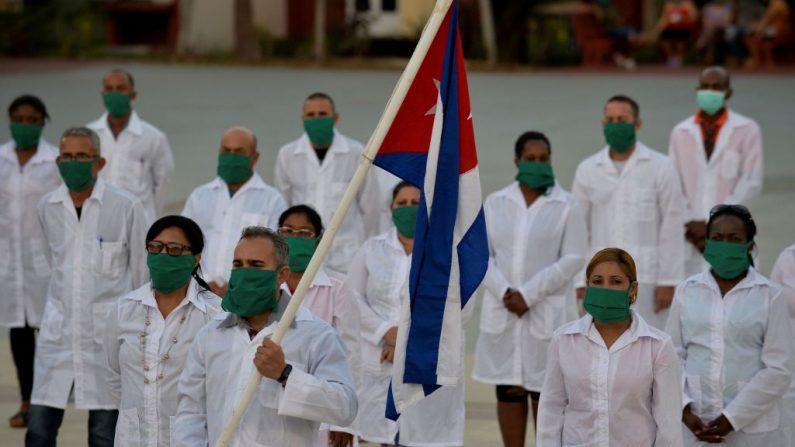 Médicos y enfermeras de la Brigada Médica Internacional Henry Reeve de Cuba participan en una ceremonia de despedida antes de viajar a Andorra para ayudar en la lucha contra la pandemia del COVID-19, en la Unidad Central de Cooperación Médica de La Habana (Cuba), el 28 de marzo de 2020. (Foto de YAMIL LAGE/AFP vía Getty Images)
