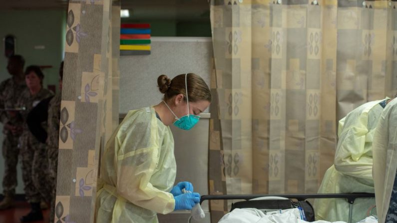 Un marinero trata a un paciente a bordo del buque hospital USNS Mercy, que fue desplegado para servir como hospital de referencia para pacientes con virus no PCCh actualmente admitidos en hospitales con base en tierra, en Los Ángeles, California, el 29 de marzo de 2020. (Marina de los Estados Unidos vía Getty Images)