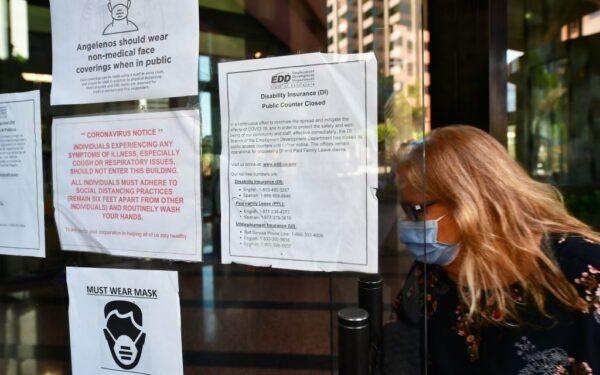 Una mujer con una mascarilla entra en un edificio donde el Departamento de Desarrollo del Empleo tiene sus oficinas en Los Ángeles, California, el 4 de mayo de 2020. (Frederic J. Brown/AFP vía Getty Images)