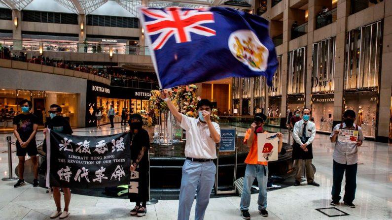 """Un manifestante prodemocrácia agita una bandera colonial británica durante un mitin """"Almuerzo contigo"""" en un centro comercial en el distrito central de Hong Kong el 1 de junio de 2020. (Issac Lawrence / AFP/Getty Images)"""