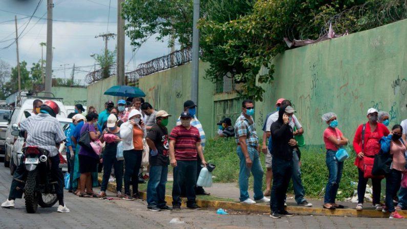 Los familiares de los pacientes esperan en fila para entrar en el Hospital Alemán-Nicaragüense que atiende a las personas infectadas con el COVID-19 en Managua, Nicaragua, el 1 de junio de 2020. (Foto de INTI OCON/AFP vía Getty Images)