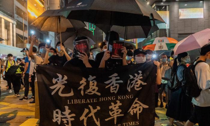 Los manifestantes sostienen una pancarta mientras marchan en una calle, durante un mitin en el distrito central de Hong Kong, el 9 de junio de 2020. (Anthony Kwan/Getty Images)