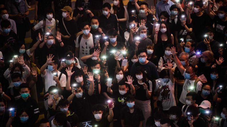Manifestantes prodemocracia sostienen sus teléfonos móviles mientras cantan durante un encuentro en el distrito de Causeway Bay de Hong Kong el 12 de junio de 2020. (Anthony Wallace/AFP vía Getty Images)