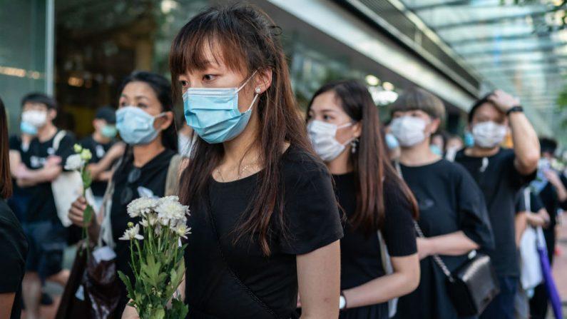 Los dolientes colocan flores durante la vigilia conmemorativa del primer aniversario de la muerte de Marco Ling-kit Leung en un centro comercial el 15 de junio de 2020 en Hong Kong, China. (Anthony Kwan/Getty Images)
