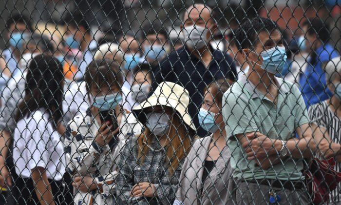 Las personas se reúnen en un área al aire libre para tomarse una prueba de hisopo, durante las pruebas masivas para el COVID-19, en Beijing, China, el 23 de junio de 2020. (NOEL CELIS/AFP a través de Getty Images)