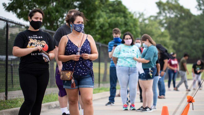Los pacientes esperan en la fila en un lugar de pruebas de COVID-19 en la Escuela Secundaria de la Academia A+ el 27 de junio de 2020 en Dallas, Texas (EE.UU.). (Foto de Montinique Monroe/Getty Images)