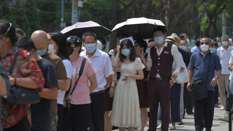 Personas haciendo cola para someterse a pruebas de hisopos COVID-19 en una estación de pruebas en Beijing, China el 30 de junio de 2020. (GREG BAKER/AFP a través de Getty Images)