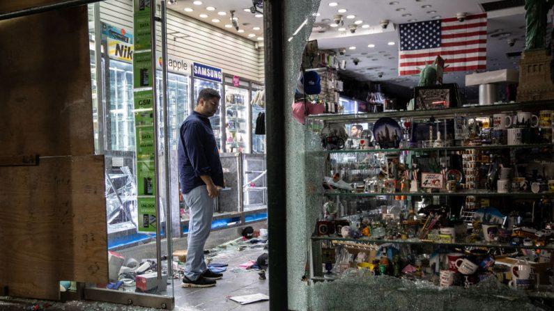 El propietario observa su tienda de recuerdos saqueada cerca de Times Square, después de una noche de protestas y vandalismo por la muerte de George Floyd el 2 de junio de 2020 en la ciudad de Nueva York. (John Moore/Getty Images)