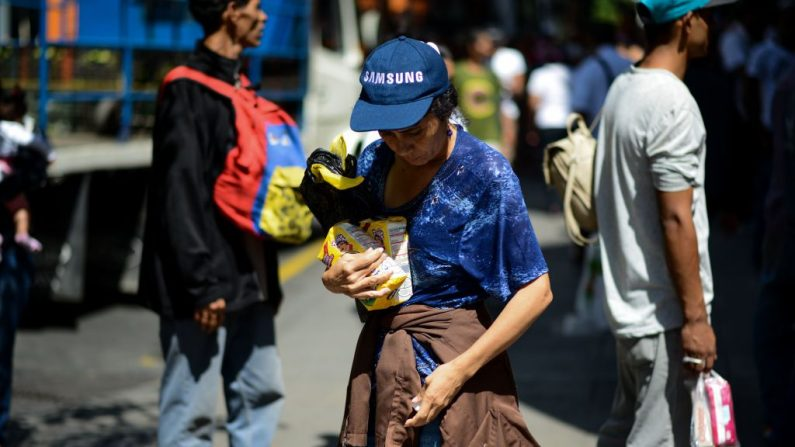 Una mujer sostiene dos bolsas de harina después de hacer cola frente a un supermercado en Caracas (Venezuela) para comprar alimentos básicos y productos domésticos el 10 de noviembre de 2017. (FEDERICO PARRA/AFP vía Getty Images)