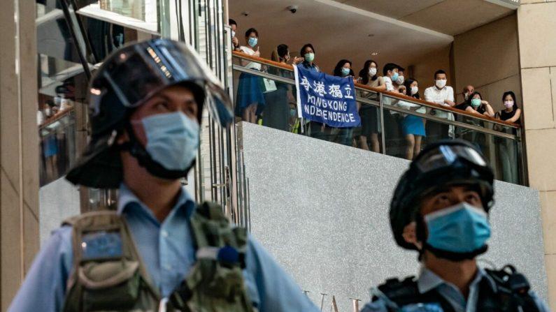 Los partidarios de la democracia sostienen una bandera de la Independencia de Hong Kong y gritan eslóganes durante un mitin contra la ley de seguridad nacional mientras la policía antidisturbios asegura un área en un centro comercial el 30 de junio de 2020 en Hong Kong. Beijing ha aprobado la controvertida ley de seguridad nacional que amenazará la autonomía y las libertades políticas de la ciudad. ( Anthony Kwan/Getty Images)