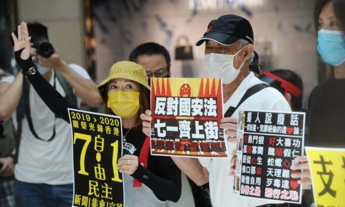 Varios manifestantes participan en una protesta a la hora del almuerzo en el distrito Central de Hong Kong el 30 de junio de 2020. Sostienen carteles que invitan a la gente a unirse a la protesta del 1 de julio. (Song Bilung/The Epoch Times)
