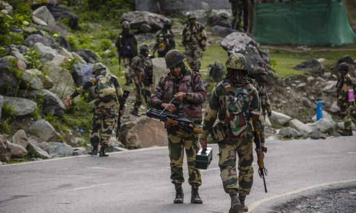 Soldados de la Fuerza de Seguridad Fronteriza de la India (BSF) patrullan una carretera mientras el convoy del ejército indio pasa por una carretera que conduce hacia Leh, que limita con China, en Gagangir, India, el 19 de junio de 2020. (Yawar Nazir / Getty Images)