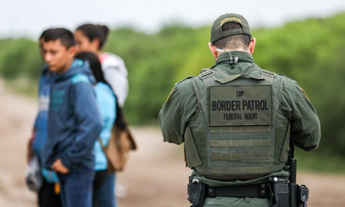 Un agente de la Patrulla Fronteriza de EE.UU. detiene a varios inmigrantes ilegales que acaban de cruzar el Río Grande desde México a Peñitas, Texas, el 21 de marzo de 2019. (Charlotte Cuthbertson/The Epoch Times)