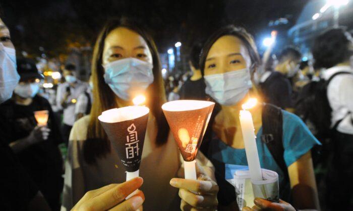 Dos personas sostienen velas durante una vigilia en el Victoria Park de Hong Kong el 4 de junio de 2020. (Song Bilung / The Epoch Times)
