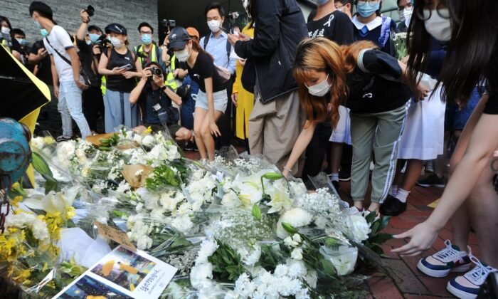 La gente deposita flores recordando la muerte de un manifestante local, cerca del centro comercial Pacific Place en Admiralty, Hong Kong, el 15 de junio. 2020. (Song Bilung/The Epoch Times)