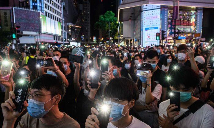 Activistas pro-democracia sostienen sus teléfonos móviles mientras cantan durante una manifestación en el distrito de Causeway Bay de Hong Kong el 12 de junio de 2020. (Anthony Wallace/AFP vía Getty Images)