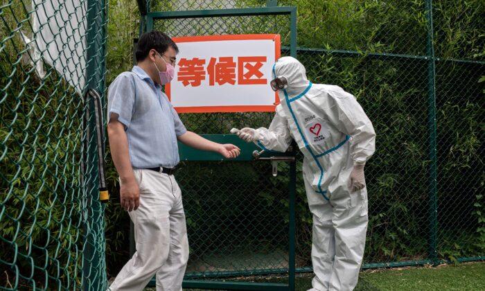 Un hombre que lleva una mascarilla se somete a un control de temperatura corporal por parte de un trabajador de la salud que lleva un equipo de protección personal (EPI), mientras entra en una zona exterior durante un test masivo de detección del virus del PCCh en el lugar de pruebas del parque forestal urbano de Xinjiekou, en Beijing, el 24 de junio de 2020. (Nicolas Asfouri/AFP vía Getty Images)