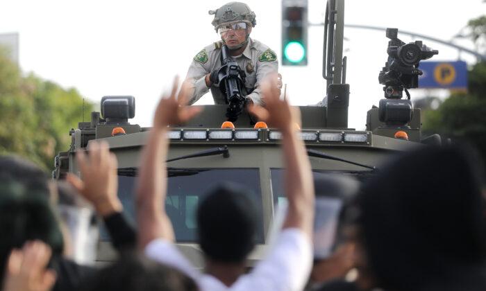 Un agente de policía apunta un arma no letal mientras varios manifestantes levantan la mano durante las manifestaciones tras la muerte de George Floyd en Santa Mónica, California, el 31 de mayo de 2020. (Mario Tama/Getty Images)
