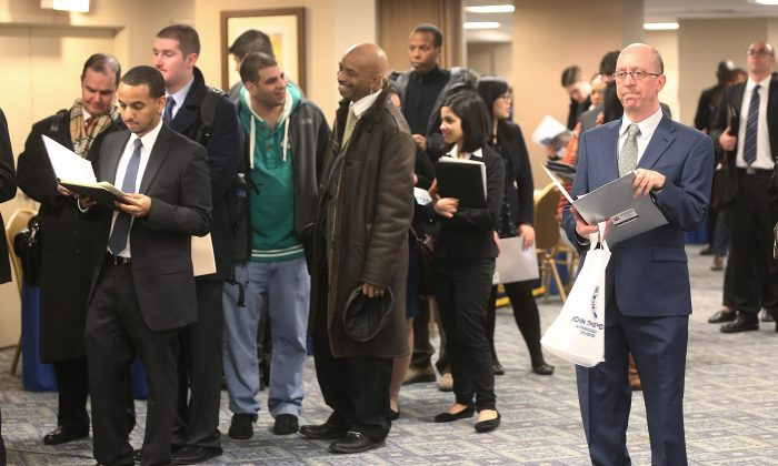 Los solicitantes esperan para conocer a posibles empleadores en una feria de trabajo en Manhattan, N.Y., el 17 de enero de 2013. (Mario Tama/Getty Images)