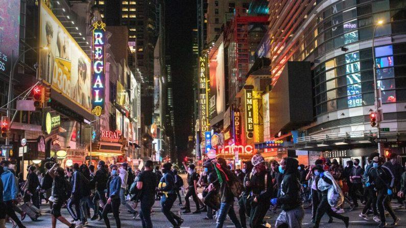 Los manifestantes se apresuran a pasar por Times Square después de las 11 p.m. ya que el toque de queda comenzó en Nueva York el 1 de junio de 2020. (John Moore/Getty Images)