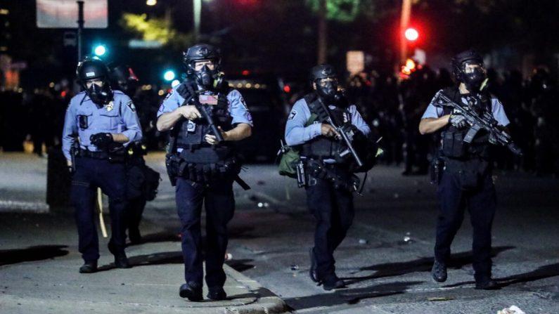 La policía retoma las calles alrededor de la medianoche después de disparar copiosas cantidades de gas lacrimógeno para dispersar a los manifestantes y alborotadores fuera del 5º distrito policial de Minneapolis durante la cuarta noche de protestas y violencia tras la muerte de George Floyd, en Minneapolis, Minn., el 29 de mayo de 2020. (Charlotte Cuthbertson/The Epoch Times)