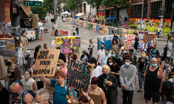 Varios manifestantes marchan a través del área conocida como la Capitol Hill Organized Protest (CHOP) en Seattle, Washington, el 24 de junio de 2020. (David Ryder/Getty Images)