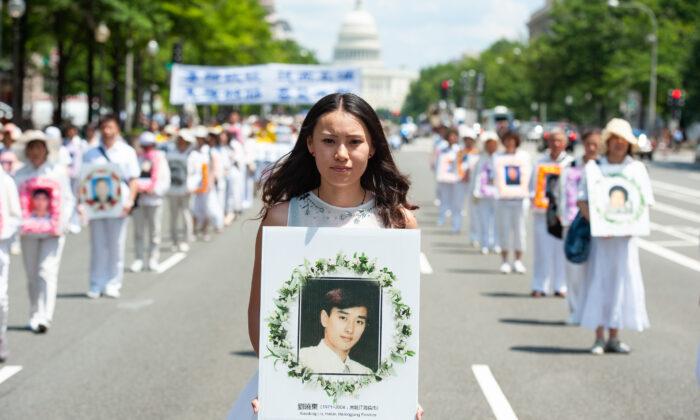 Una mujer sostiene una foto de un hombre asesinado por la persecución del régimen chino a Falun Gong, durante un desfile en Washington el 17 de julio de 2014. (Larry Dye/The Epoch Times)