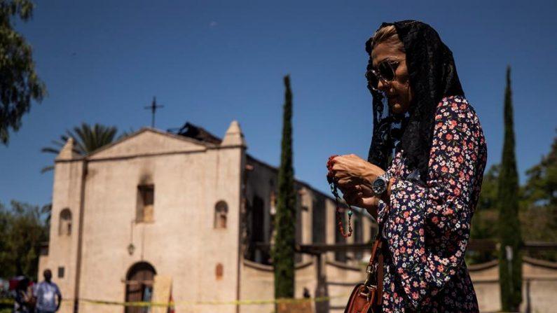 Una mujer reza mientras asiste a una misa celebrada frente a la Misión de San Gabriel destruida por un incendio en San Gabriel, California.