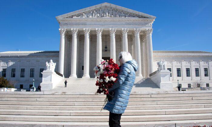 Una mujer ayuda a depositar 3000 claveles para representar los aproximadamente 3,000 abortos que ocurren en Estados Unidos cada día, en el 46º aniversario de la decisión Roe v Wade, frente a la Corte Suprema de Estados Unidos en Washington el 22 de enero de 2019. (Jim Watson/AFP vía Getty Images)