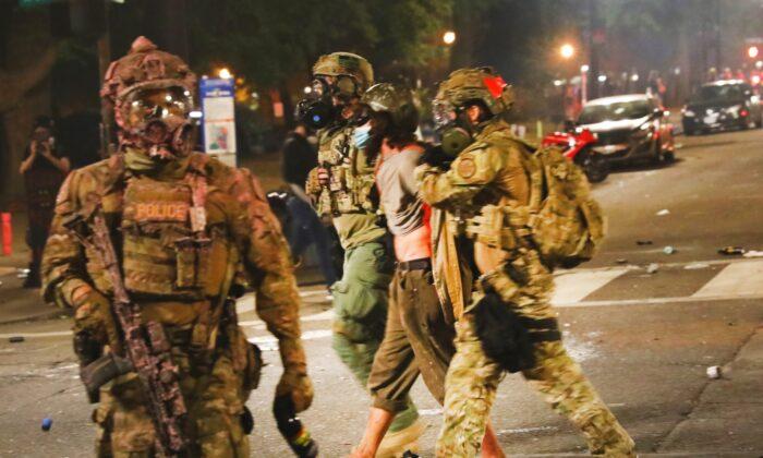 Agentes federales arrestan a manifestantes frente al tribunal federal Mark O. Hatfield, en el centro de Portland, mientras la ciudad experimenta otra noche de disturbios, el 25 de julio de 2020. (Spencer Platt/Getty Images)