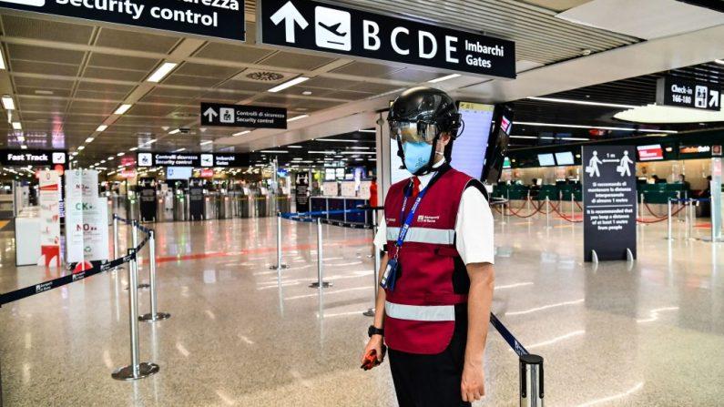 Un empleado del aeropuerto de Fiumicino que lleva un termoescáner portátil para examinar a los pasajeros y al personal en relación con el COVID-19, se encuentra preparado en las puertas de embarque el 5 de mayo de 2020 en el aeropuerto de Fiumicino en Roma (Italia) durante el cierre del país con el fin de frenar la propagación de la infección por COVID-19, causada por el virus del PCCh. (Foto de ANDREAS SOLARO/AFP vía Getty Images)