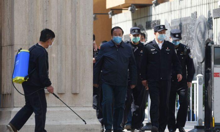 Agentes de policía y funcionarios salen de una escuela secundaria mientras un hombre (izq) desinfecta la entrada, en Beijing el 27 de abril de 2020. (Greg Baker/AFP a través de Getty Images)