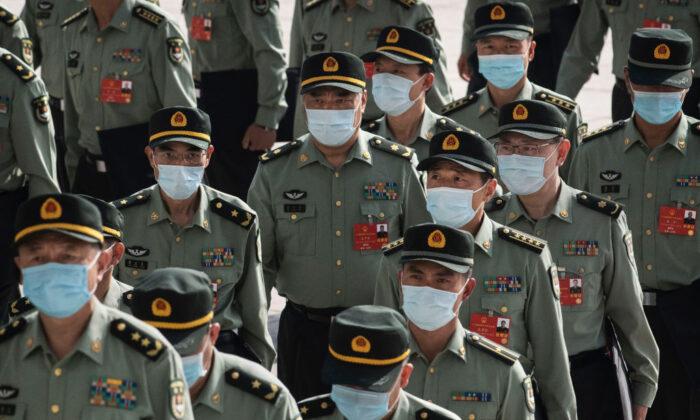Delegados de las Fuerzas Armadas de China llevan mascarillas al llegar a la sesión de apertura de la Asamblea Popular Nacional en el Gran Salón del Pueblo de Beijing, el 22 de mayo de 2020. (Kevin Frayer/Getty Images)