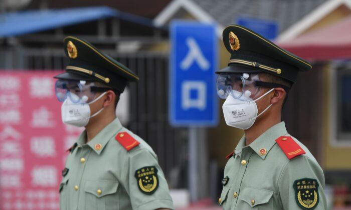 Los agentes de la policía paramilitar usan mascarillas faciales y gafas protectoras mientras hacen guardia en una entrada al mercado cerrado de Xinfadi en Beijing el 13 de junio de 2020. (GREG BAKER/AFP a través de Getty Images)